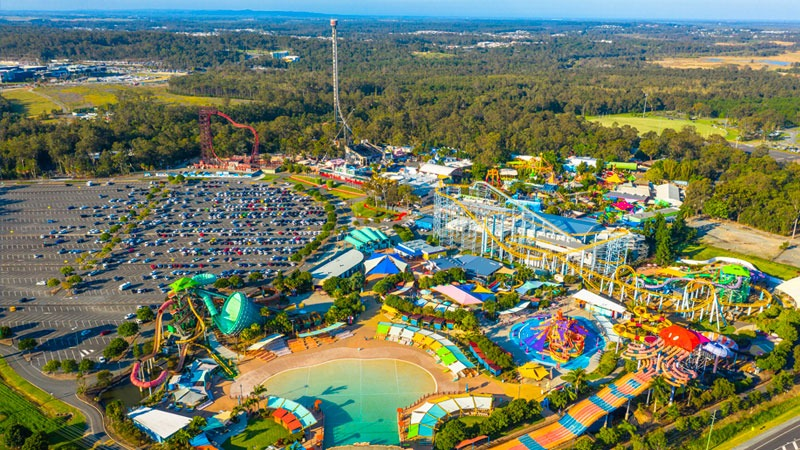 ▲ An aerial shot of Dreamworld showing roller coasters, water park, cars in the parking lot and the Gold Coast hinterland in the distance.