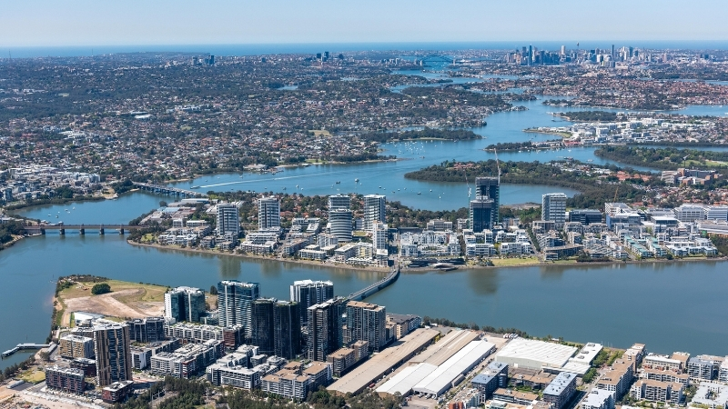 An image from up high looking at Rhodes and the Parramatta River with Sydney CBD in the distance.