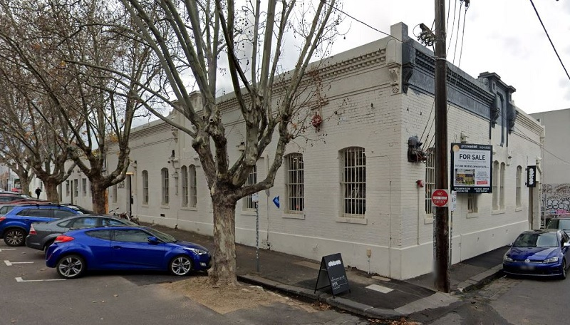 The former shirt factory built along both Gore and Argyle Streets in Fitzroy was painted white and has a series of old trees outside.