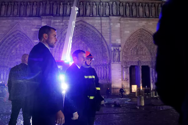 French President Emmanuel Macron speaks with firemen at the cathedral.