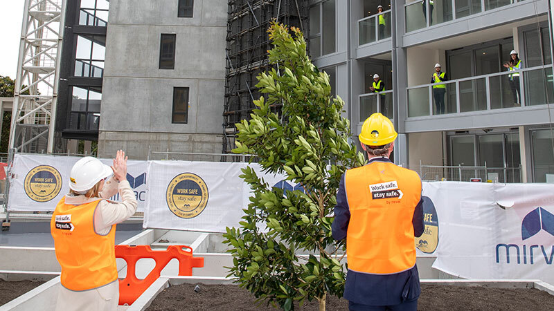 Image of Mirvac chief executive and managing director Susan Lloyd-Hurwitz and NSW Treasurer Dominic Perrottet at the socially-distanced topping out / tree planting ceremony for Pavilions at Sydney Olympic Park, congratulating workers standing on the balconies.