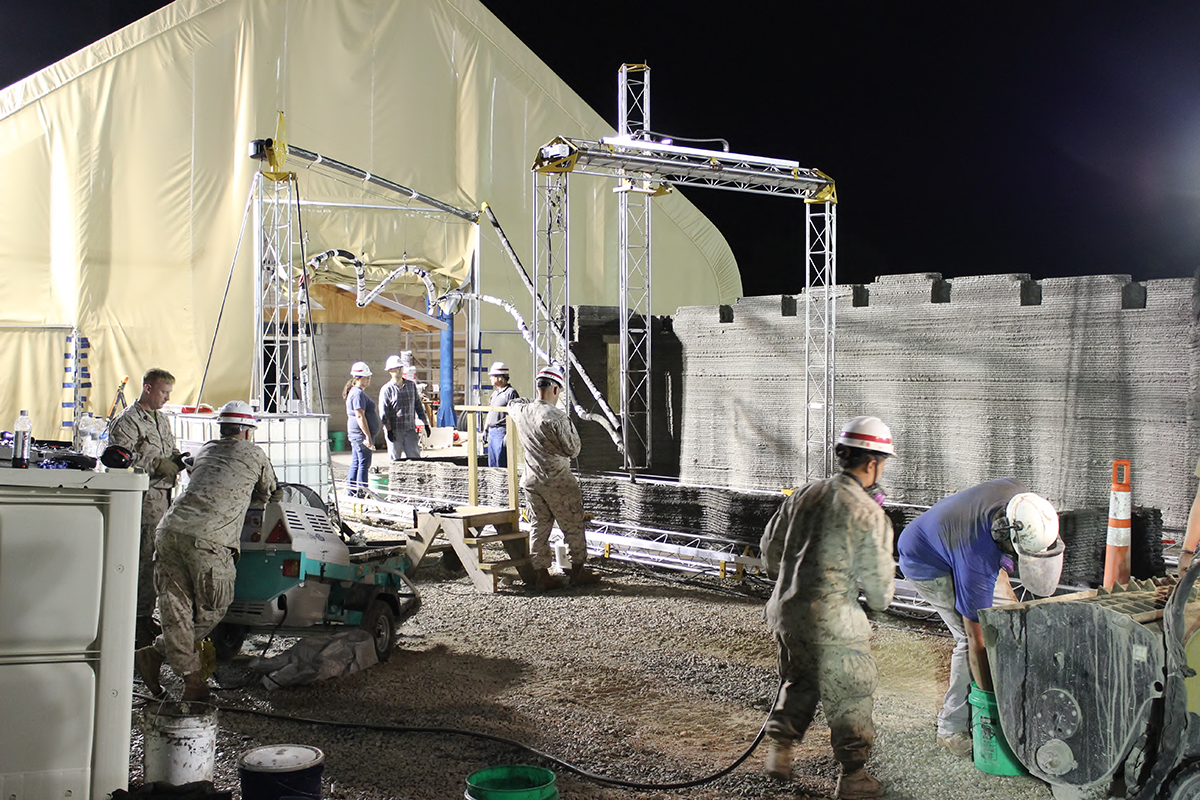 The world's largest concrete 3D printer constructs a 500-square-foot barracks hut.