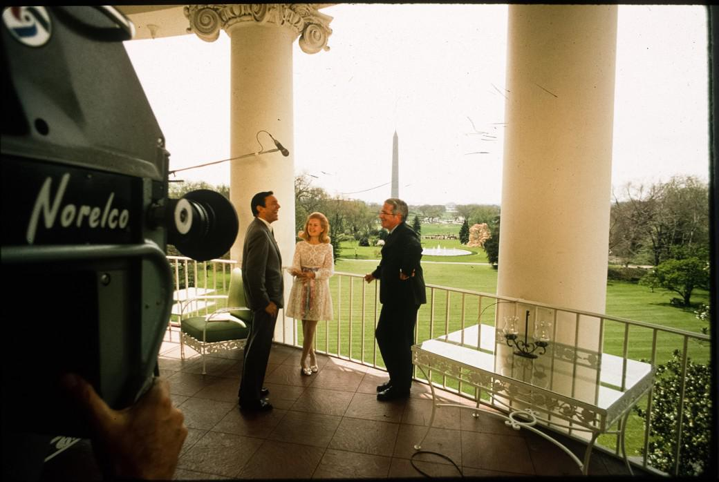 Tricia Nixon speaks with Mike Wallace and Harry Reasoner on the Truman Balcony. The White House south grounds, the Washington Monument and Jefferson Monument are all visible from President Truman's 1947 addition to the house. Source: White House Historical Association