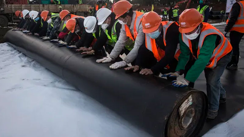 Construction workers roll out damp-proof lining as they build the Huoshenshan hospital in Wuhan. Image: Getty Images
