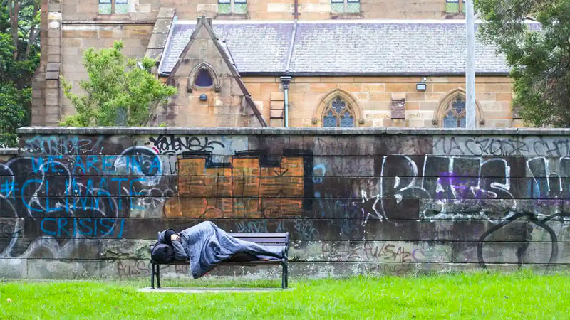▲ A homeless man sleeps on a park bench in Sydney in March. Image: Getty Images.