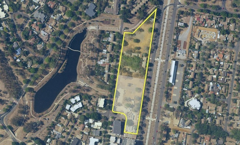 Aerial image of a block of land situated between a lake and railway which is surrounded by houses.