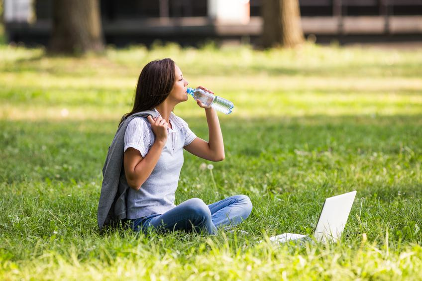 Beautiful businesswoman is drinking water and resting from work at the park.