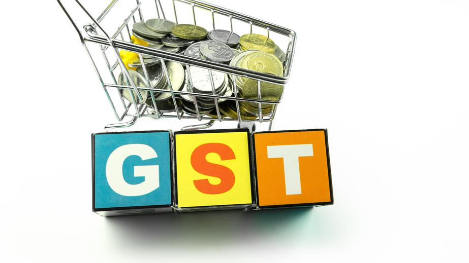 GST alphabet letters and mini shopping trolley loaded with coins