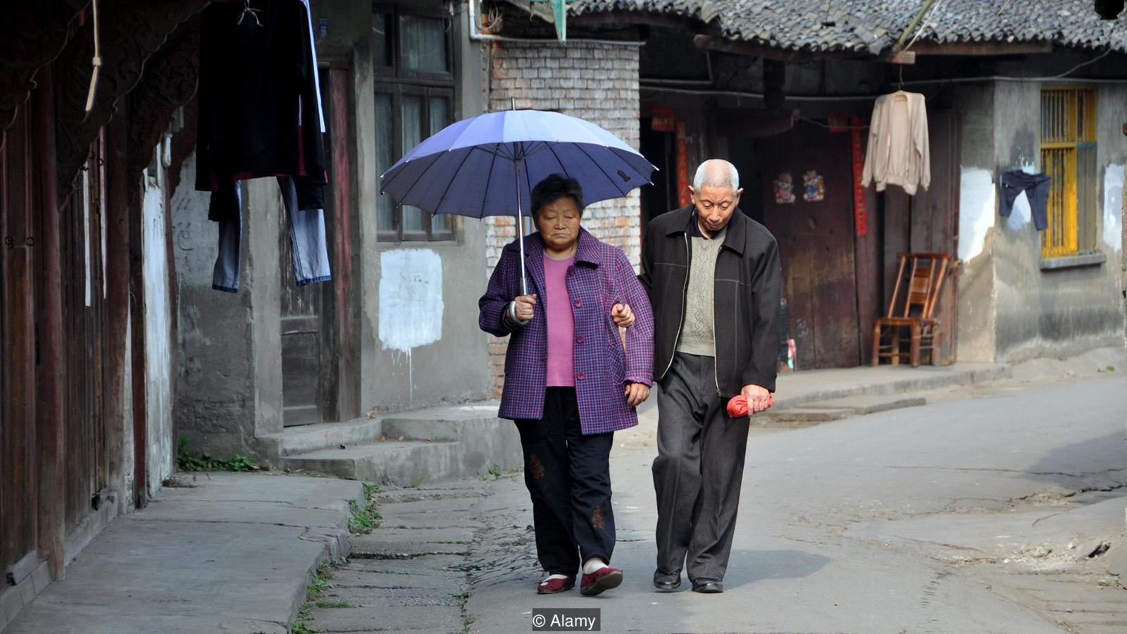 PENGZHOU, CHINA: A loving elderly couple walking along Hua Lu Street